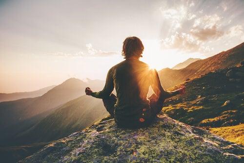 Hombre sin miedo a las alturas meditando en la montaña