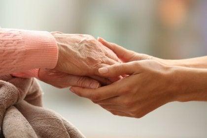 Joven agarrando las manos de una anciana con actitudes cariñosas