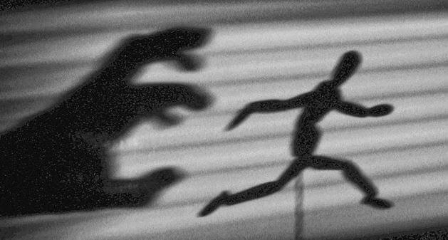 La sombra de una mano atrapando a un muñeco