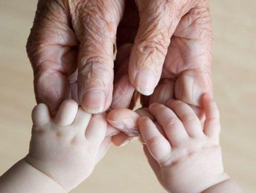 manos de un anciano cogiendo las de un bebé