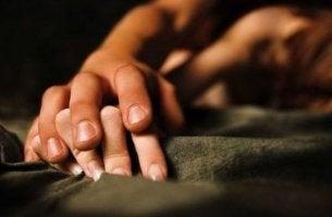 Manos entrelazadas de dos personas haciendo el amor