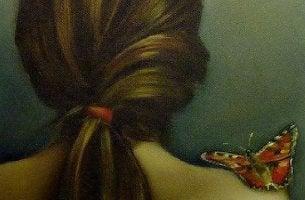 Mariposa sobre un hombro desnudo para representar la relación entre piel y emociones
