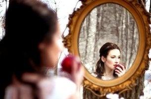 mujer ante un espejo mordiendo una manzana