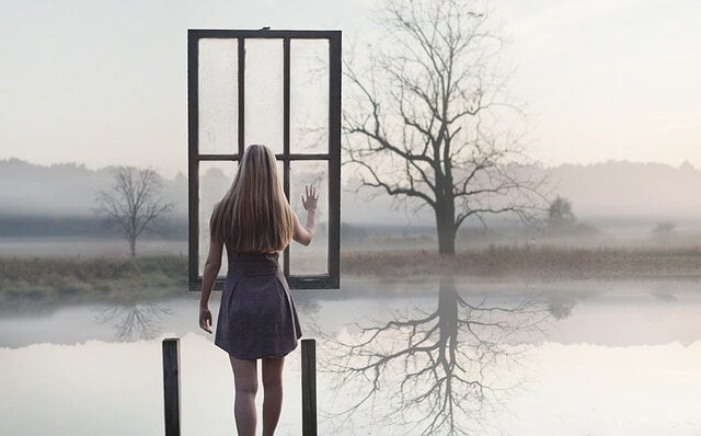 mujer ante una ventana suspendida en el aire representando la comunicación asertiva