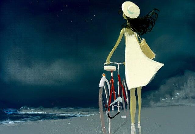 mujer paseando en bicicleta por la playa pensando en cambiar de vida