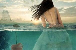 Mujer en el agua al lado de un corazón sumergido