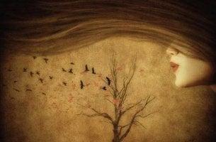 mujer soplando las ramas de un árbol