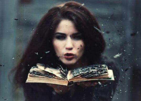 Mujer soplando sobre un libro