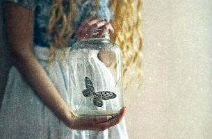 Joven con un tarro de cristal con una mariposa simbolizando un trauma