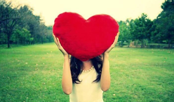Mujer con alta autoestima sujetando un corazón enorme