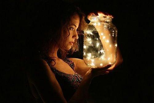 mujer sujetando un tarro con luciérnagas