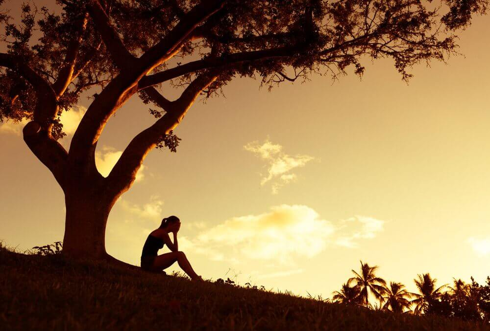 Mujer triste bajo un árbol pensando en el suicidio