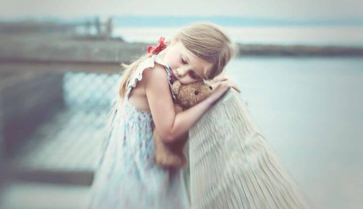 niña abrazada a un oso de peluche