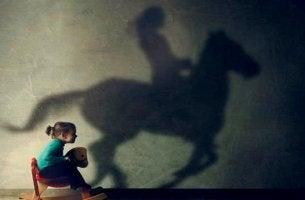niña sobre caballito de madera reflejando la sombra de un jinete adulto