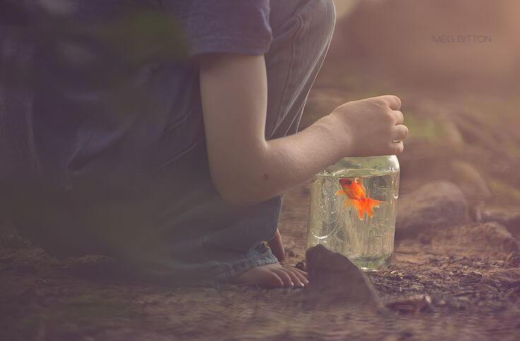 niño tapando un frasco de cristal con un pez dentro representando los valores del cariño