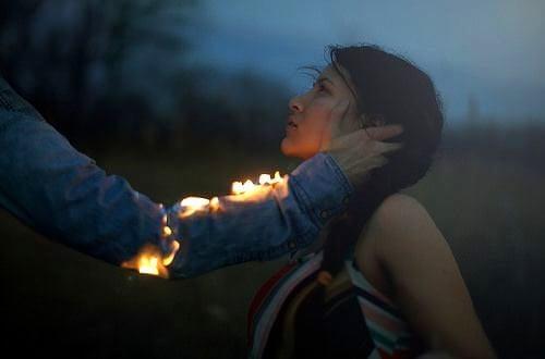 pareja mirándose con un brazo en llamas