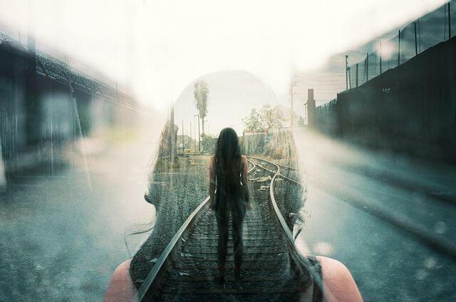 Mujer de pie en una vía del tren