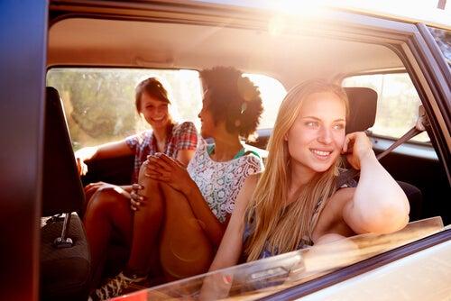 Amigos sentados en un coche de vuelta de sus viajes