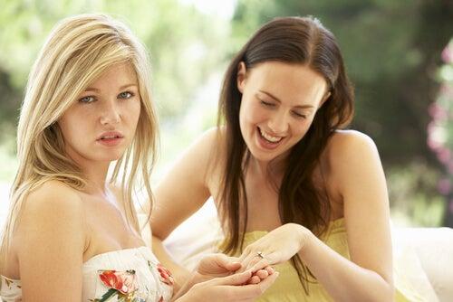 Chica sintiendo envidia de la otra persona por su anillo