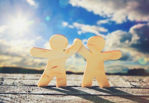 Dos muñecos dándose la mano en símbolo de amistad