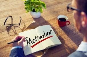 Hombre escribiendo en una libreta la palabra motivación