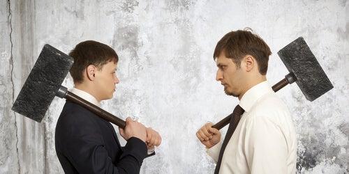 Hombres muy temperamentales con un martillo enfrente uno del otro