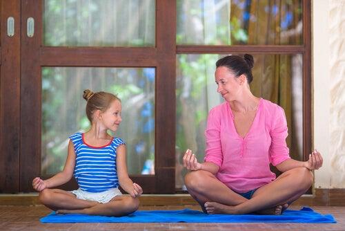 Madre enseñando a meditar a su hija