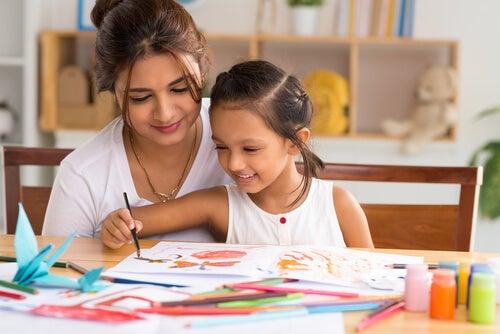 Madre viendo como su hija pinta una lámina de colores