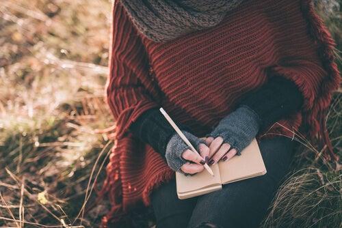 Manos de mujer escribiendo en una libreta en el campo