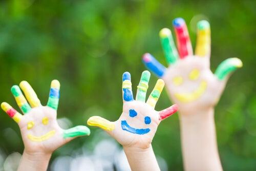 Manos de niños pintadas con caras sonrientes