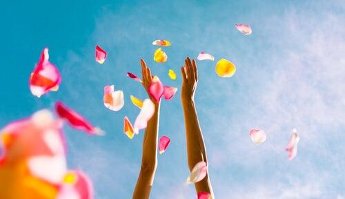 Manos en alto tirando pétalos de flores
