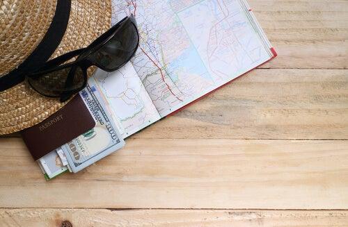 Mapa billetes de avión sombrero y gafas de un viajero encima de la mesa