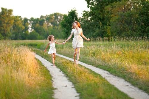 Mujer caminando con hijo por el campo