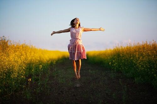 Mujer caminando por campo de espigas con los brazos abiertos