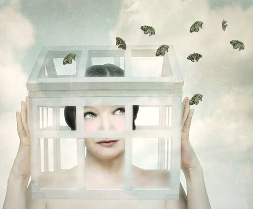 Mujer con la cabeza encerrada en una jaula con mariposas alrededor
