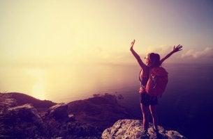 Mujer con los brazos abiertos en la cima de una montaña