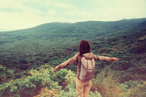 Mujer con mochila en la cima de una montaña