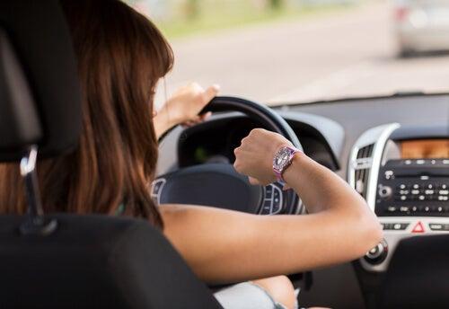 Mujer conduciendo con prisas conduciendo mirando el reloj