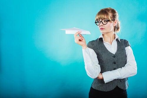 Mujer con un avión de papel en la mano