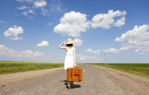 Mujer con un gorro y una maleta por la carretera