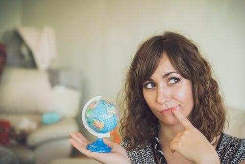 Mujer con una bola del mundo pensando en su próximo viaje