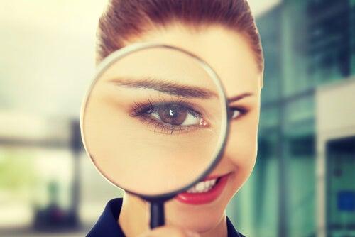 Mujer con una lupa sintiendo curiosidad