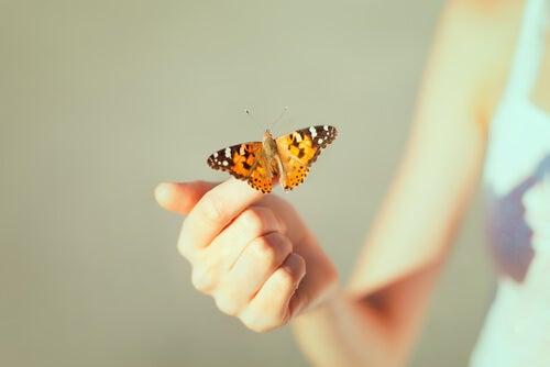 Mujer con una mariposa en su mano