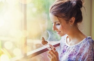 Mujer con una mariposa pensando en sus sueños