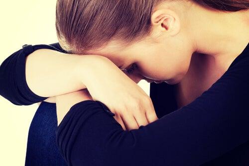 Mujer confusa con la cabeza hacia abajo pensando en su fracaso