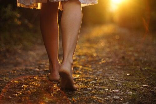 Mujer descalza andando por un camino