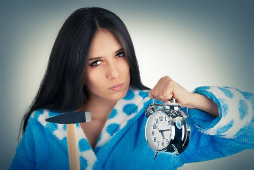 Mujer enfadada con un martillo en una mano y un reloj en la otra