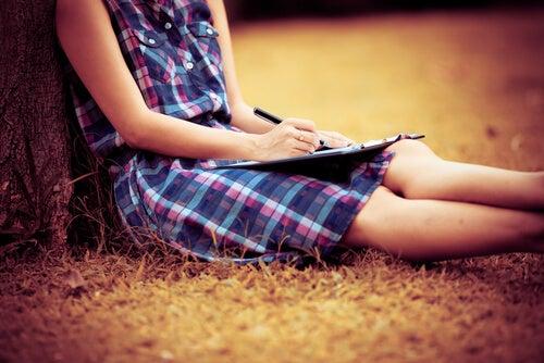 Mujer escribiendo sus objetivos en una libreta