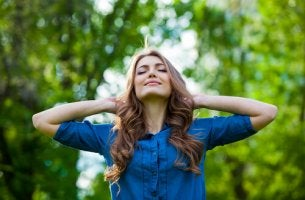 Mujer feliz con los ojos cerrados y las manos en la cabeza