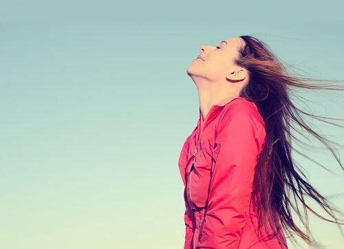 Mujer feliz respirando al aire libre